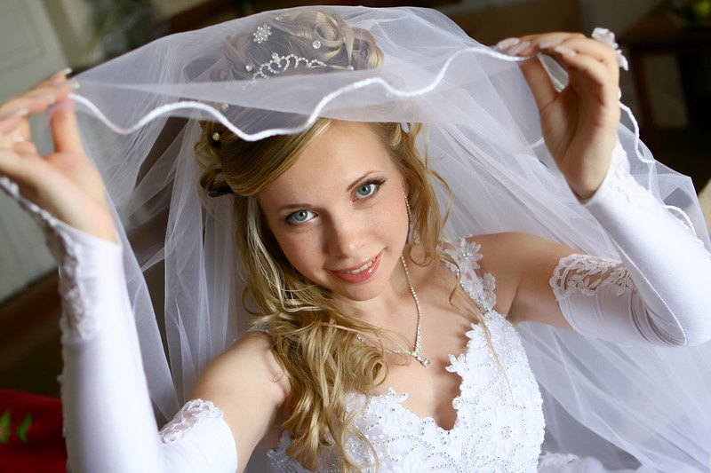 This image shows a smiling blond bride in a white dress and long gloves lifting a white veil from her face, representing the best bridal affiliate programs.