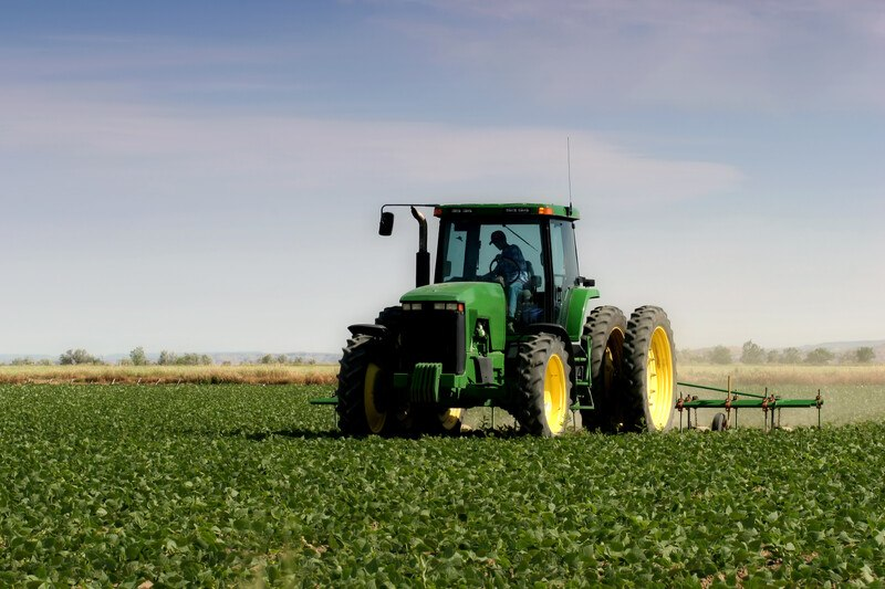 This photo shows a large green tractor with yellow and wheels and black tires pulling some farming equipment through a green field, representing the best farming affiliate programs.
