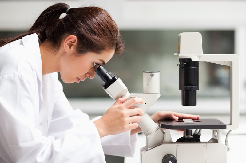 This image shows a dark-haired woman in a ponytail and a white lab coat looking into a white telescope in a laboratory, representing the best science affiliate programs.