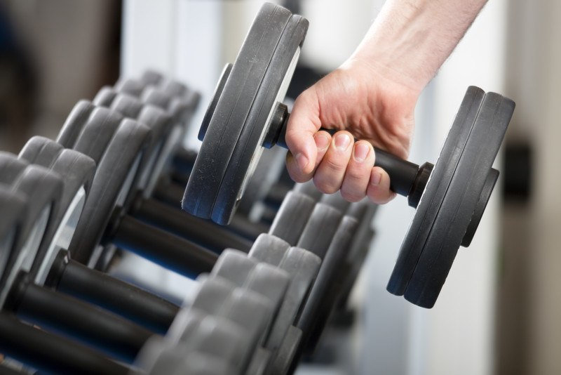 This photo shows a hand pulling a dark gray weight off a rack of hand weights, representing the best workout affiliate programs.