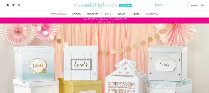 This screenshot of the home page for My Wedding Favors has a white header and navigation bar above a pink sales announcement and a photo of a row of card boxes in various styles and colors in front of a pink fabric backdrop with pink flower decorations and a garland made from sparkly gold circles.