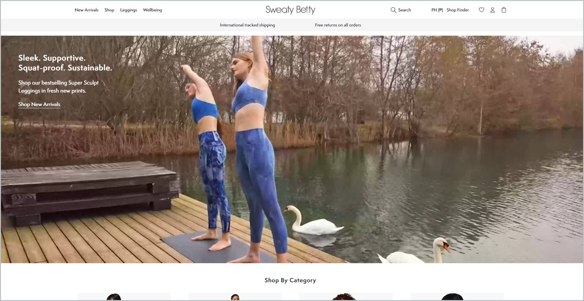 screenshot of Sweaty Betty homepage, with white header with the website's name and main navigation menu, it also features a couple of women wearing sports bra and leggings, stretching on a yoga mat