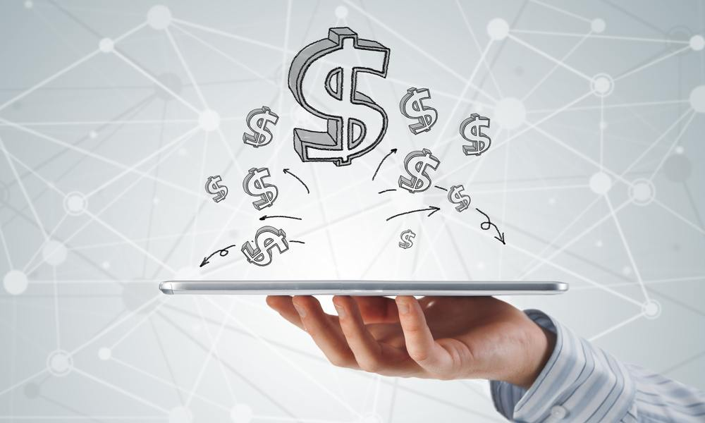 A hand holding a tablet with dollar signs