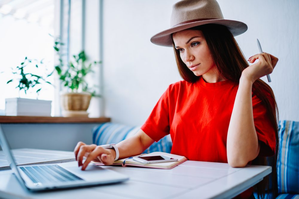 Woman in a red shirt and hat working online