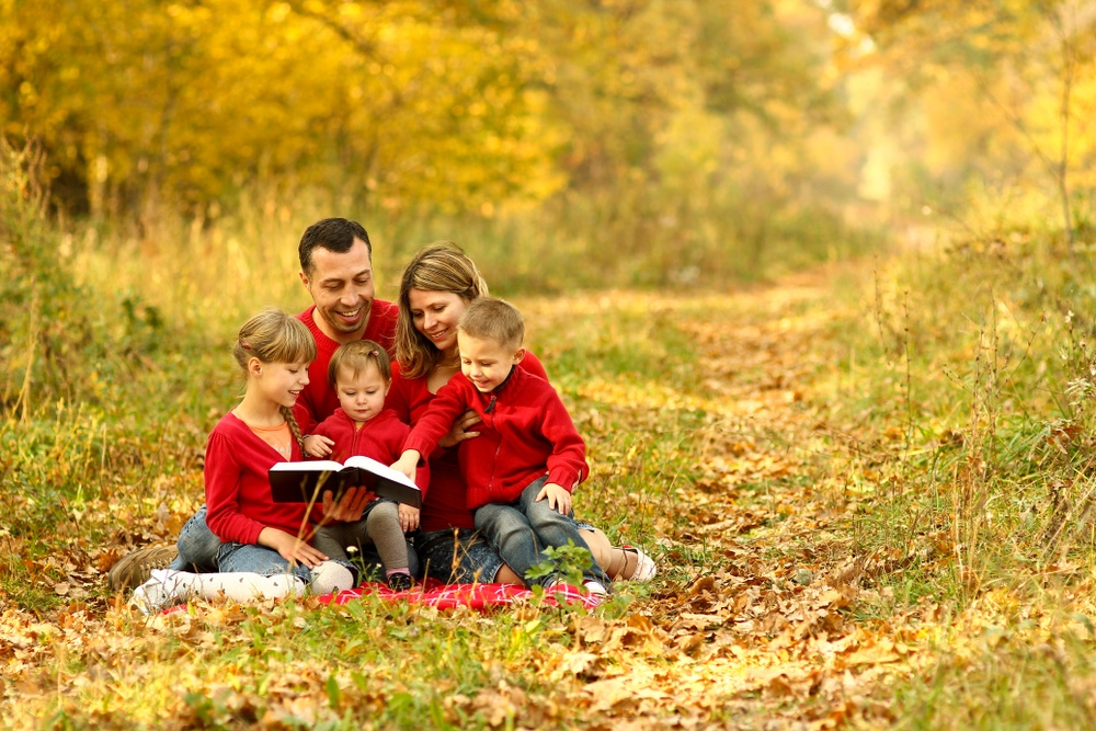 christian family photo in forest reading bible with matching red shirts