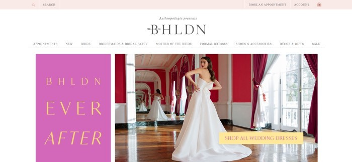 "This screenshot of the home page for BHLDN has a pink search bar at the top of the page, a white navigation bar with the logo in black, and a photo of a dark-haired woman in a white wedding gown standing in a red and white room with a large window, looking at herself in the mirror, next to a pink section with yellow text reading ""BHLDN Ever After."""