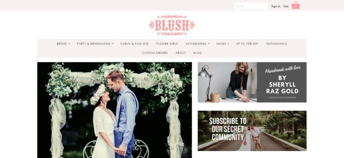 This screenshot of the home page for Blush Fashion boutique has a gray search bar header and navigation bar, a pink logo, and a white background with a photo of a man and woman in wedding attire standing in front of an arch decorated with white fabric and flowers on the left side of the page and a photo of a smiling blond woman in black and gray clothing working on designing a wedding dress on the right side of the page, along with an announcement for handmade dresses.