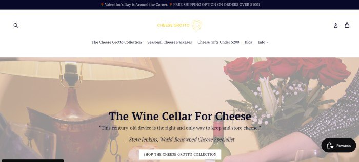 This screenshot of the home page for Cheese Grotto has a black header, a white navigation bar, and a photo showing a lit lamp, red roses, and a serving tray of wine and cheese, along with black text describing cheese grottos as wine cellars for cheeses.