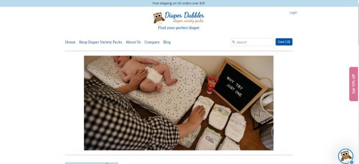 "This screenshot of the home page for Diaper Dabbler has a blue header announcing free shipping, a white background and navigation bar with blue text, and a photo of a baby lying on a black and white changing pad, near a small blackboard reading ""Why Try Just One"" and a mother's hands reaching for one diaper from a two rows of diaper samples."