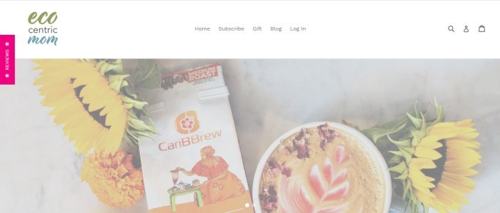 This screenshot of the home page for Ecocentric Mom has a white navigation bar above a translucent photo of sunflowers, a package of coffee, and a cup of coffee with flower petals floating on the surface.