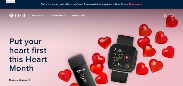 This screenshot of the home page for Fitbit has a black header announcing the new Versa 2 smartwatch above a photo with a pink background, red hearts, and two devices with heart monitors, along with black text inviting customers to put their hearts first.