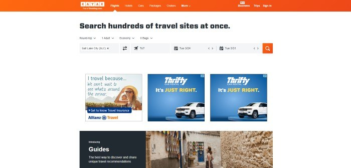 This screenshot of the home page for Kayak has an orange navigation bar above a white background with black text and black and gray search options, as well as two rows of smaller images with travel company advertisements, including a travel agency and car rentals, and a photo of a woman staring at some plates on a plastered wall in a narrow street.