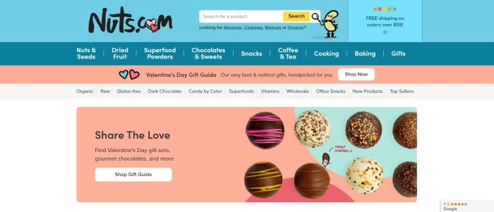 This screenshot of the home page of Nuts.com has a light blue header, a darker blue navigation bar, and coral and aqua elements throughout the page, including a secondary navigation bar and a photo section showing several types of chocolates with black text inviting shoppers to share the love and buy a gift for Valentine's Day.
