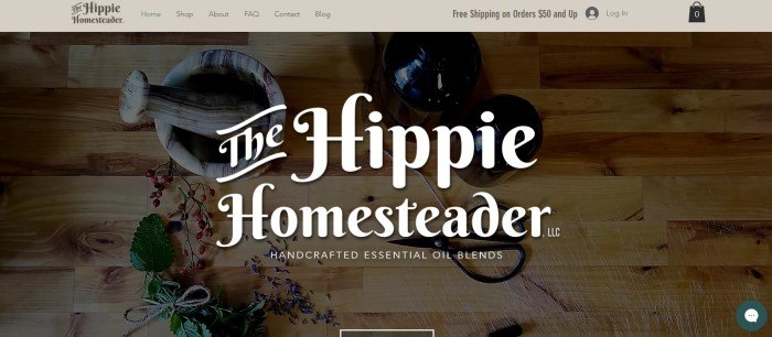 This screenshot of the home page for the Hippie Homesteader has a light brown navigation bar above a dark-filtered overhead photo of herbs, essential oil bottles, and a mortar and pestle on a wooden table, behind white words announcing The Hippie Homesteader essential oil blends.