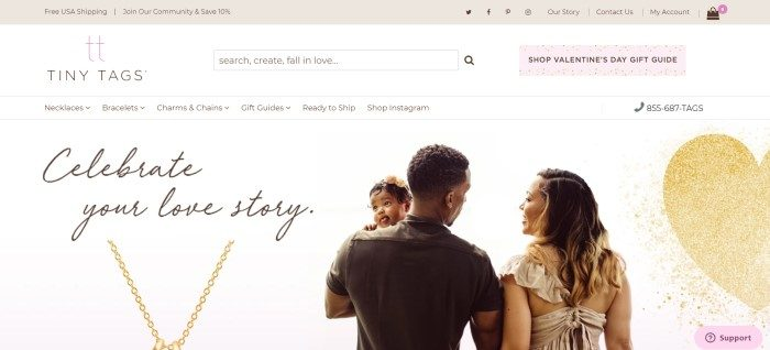 "This screenshot of the home page for Tiny Tags has a beige header announcing free shipping, a white navigation bar, and a white background with a photo of the backside of a dark-skinned father holding a dark-skinned baby with flowers in her black hair, as he walks beside a smiling dark-skinned woman in a tan shirt, next to text reading ""Celebrate your love story"" and a photo of a gold chain."