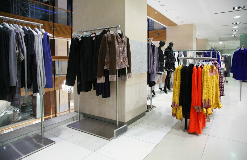 This photo shows a corner of a department store containing women's clothing in black, brown, red, and yellow, representing the best department store affiliate programs.