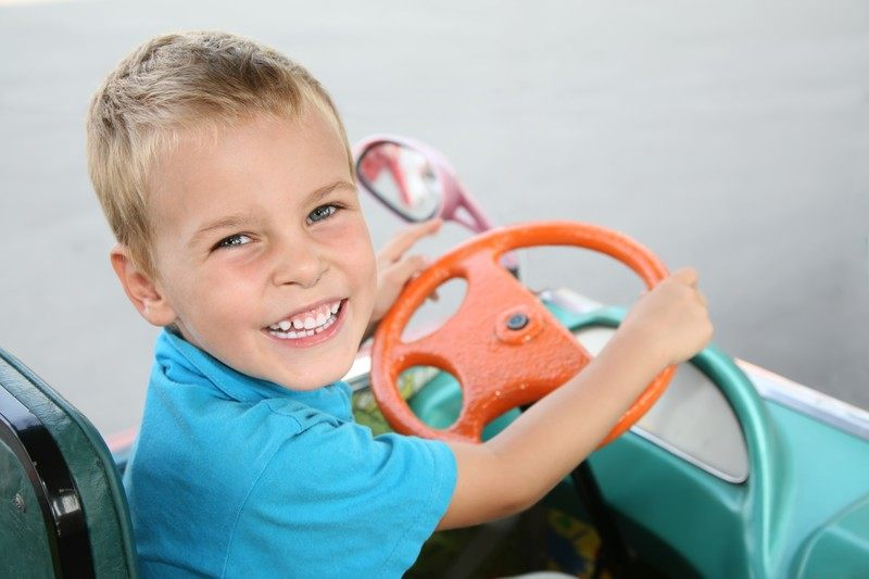 This photo shows a smiling blonde boy in a blue shirt sitting inside a theme park bumper car with an orange steering wheel, representing the best Disney affiliate programs.