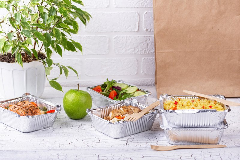 This photo shows four trays of food in foil containers sitting on a white table, along with a green apple, a house plant, and a brown paper bag, in front of a white brick wall, representing the best food delivery app affiliate programs.