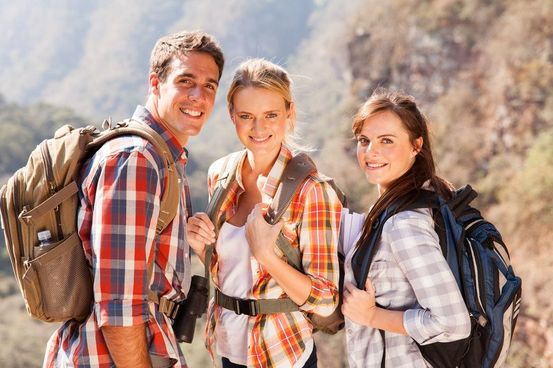 This photo shows two smiling women and a smiling man all wearing flannel shirts and backpacks on a mountain hiking trail, representing the best hiking affiliate programs.