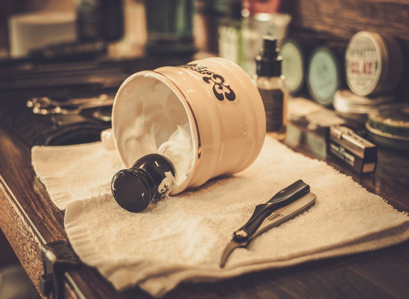 This photo shows a cream-colored shaving mug turned on its side, showing the shaving cream and a dark-handled shaving brush, lying on a white towel next to a pair of clippers on what appears to be a man's dresser, representing the best men's grooming affiliate programs.