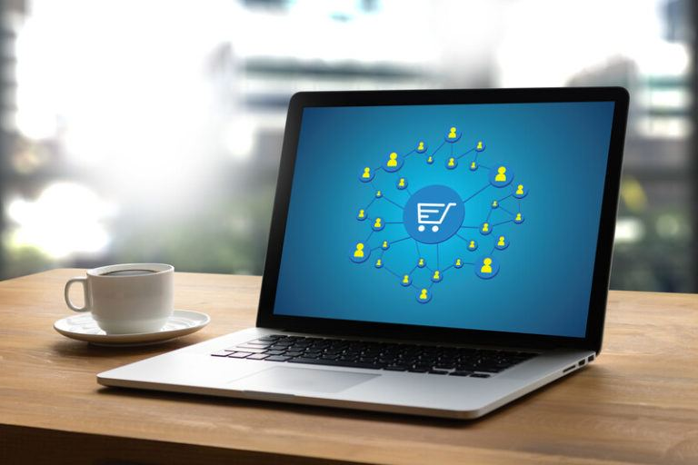 This photo shows an open laptop on a wooden desk next to a white teacup and saucer, and the laptop screen is blue with a shopping cart icon in the center and several yellow icons indicating shoppers surrounding it, representing the best online shopping affiliate programs for coronavirus.
