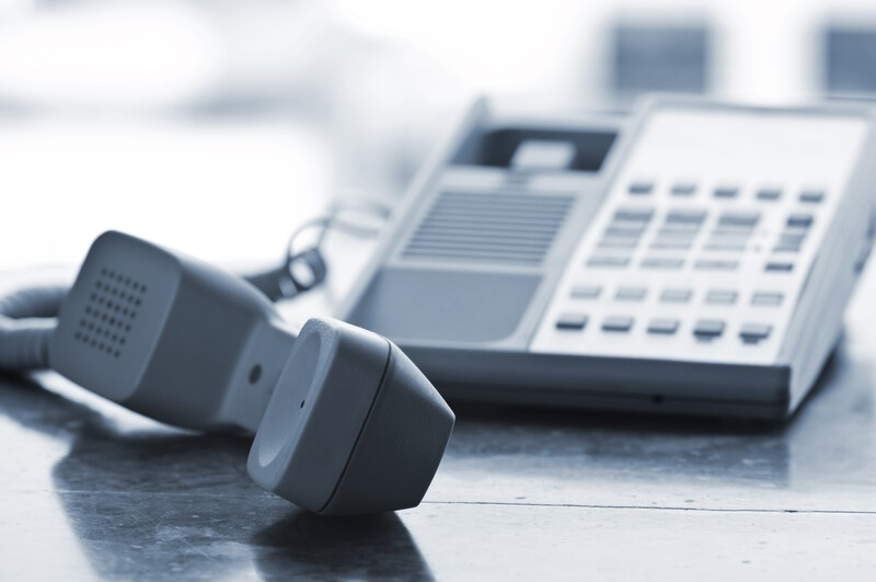 This photo shows a gray telephone handset lying on a table next to the base, representing the best telecom affiliate programs.