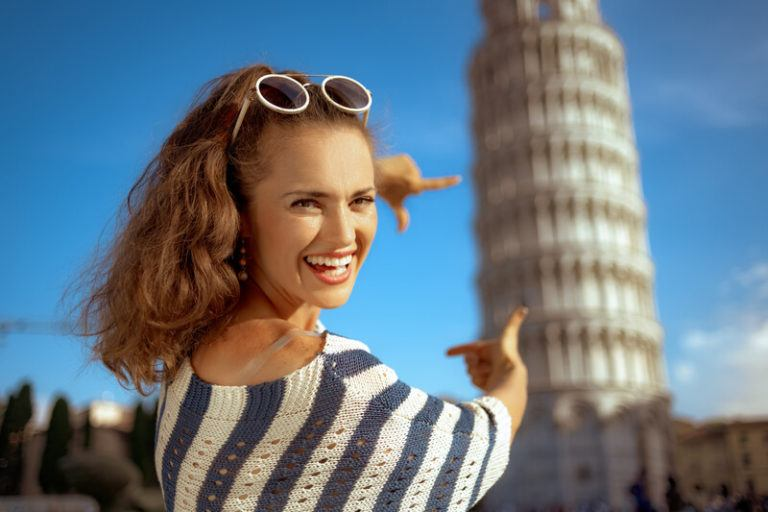 This photo shows a smiling woman with sunglasses on her forehead and a black and white sweater making a picture frame with her fingers in front of the Tower of Pisa, representing the best tour affiliate programs.