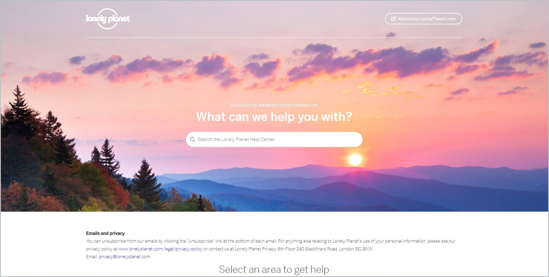 screenshot of Lonely Planet homepage featuring an image of the sky with clouds and the sun rising above the mountain ranges