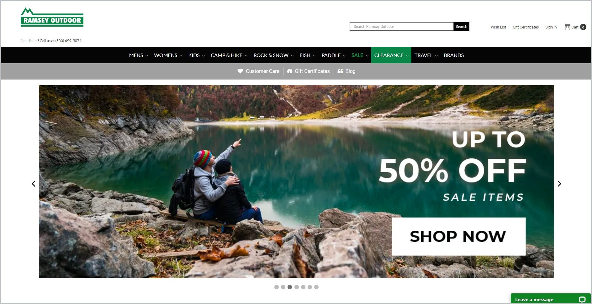 screenshot of Ramsey Outdoor homepage, with white header bearing the website's name and search bar, underneath it is the black main navigation bar, it showcases a picture of a couple looking over a lake outdoors