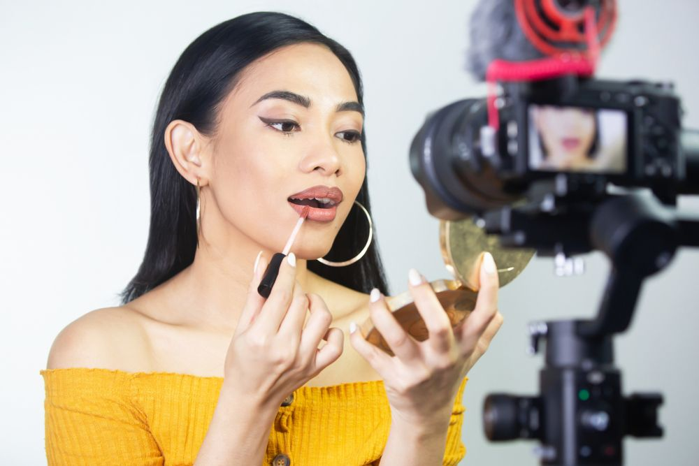 asian beauty guru putting on lipstick in front of the camera recording a video tutorial