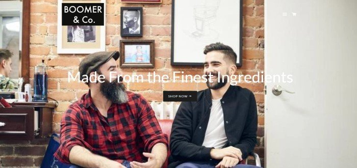 This screenshot of the home page for Boomer & Co. has a large photo of two bearded men laughing and talking in front of a brick wall in what appears to be the waiting area of a barber shop, behind white text announcing that the products are made from the finest ingredients and a menu list on the upper right side of the page.