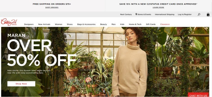 This screenshot of the home page for Century 21 has a gray header, a white search bar, and a photo of a woman with dark curly hair and a cream-colored sweater standing in greenhouse in front of a window and several plants, along with white text announcing a 50% off sale.