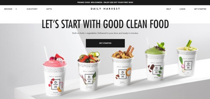 This screenshot of the home page of Daily Harvest has a black header with a promo code, a white navigation bar, and a photo of several cups of Daily Harvest products in a row with a gray background, along with black text announcing clean eating and a black call to action button.