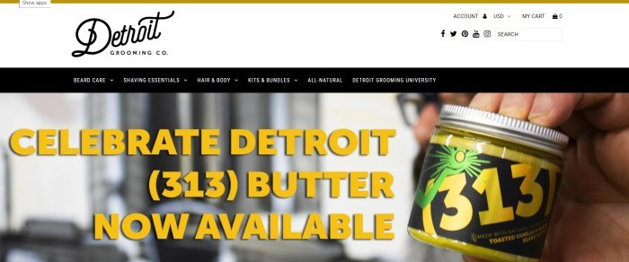This screenshot of the home page for Detroit Grooming has a white header, a black navigation bar with white lettering, and a photo of a man's hands holding a jar of 313 beard butter, along with text in yellow lettering inviting customers to try the beard butter.