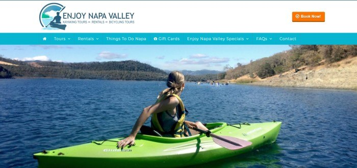 This screenshot of the home page for Enjoy Napa Valley has a white header, a turquoise navigation bar with white text, and a large photo of a blond woman in a green kayak on a lake looking over her shoulder toward other kayakers on the far side of the lake, which is surrounded by forested mountains.