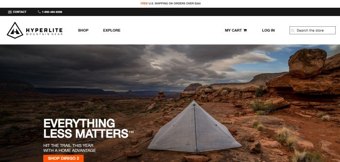 This screenshot of the home page for Hyperlite Mountain Gear has a white and black header, a white navigation bar, and a large photo of a tent pitched in a desert as a storm approaches, next to white text that reads 'Everything less matters' and an orange call-to-action button.