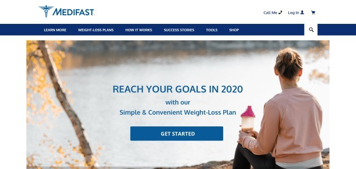This screenshot of the home page for Medifast has a white header, a blue navigation bar, and a photo of a woman sitting near a lake holding a shaker bottle with brown liquid in it, along with blue text inviting people to reach their weight loss goals and a blue call to action button.