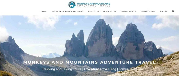 This screenshot of the home page for Monkeys And Mountains has a white header and navigation bar above a photo of rocky mountain tops with white lettering announcing trekking and hiking tours as well as lemur tours.