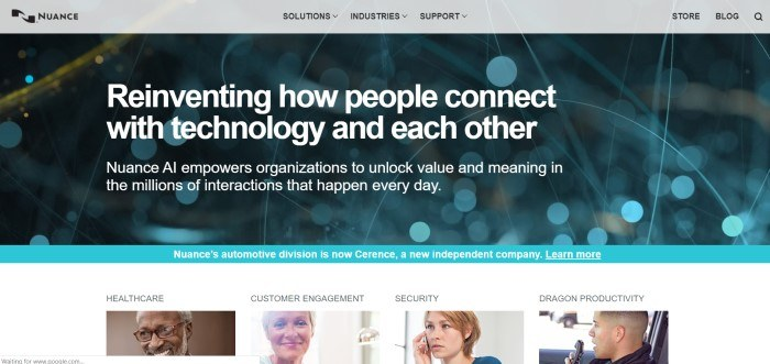 This screenshot of the home page for Nuance has a gray navigation bar above an out-of-focus photo of what appears to be blue and gold wires, behind white text describing Nuance AI as a way to reinvent how people connect, above a row of photos showing smiling people along with text indicating different segments of the Nuance company.