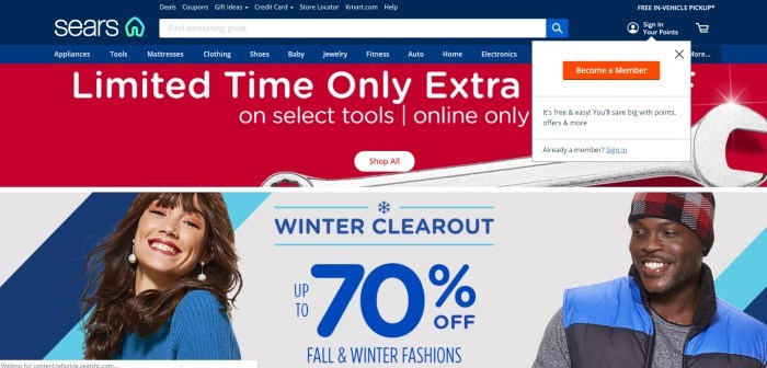This screenshot of the home page for Sears has a dark blue navigation bar and search bar, a lighter blue secondary navigation bar, a white drop-down box inviting customers to become a member, a red section with white text announcing a limited time deal, and a photo of a smiling dark haired woman in a blue sweater standing near a smiling dark-skinned man in a black and red hat and blue jacket, as well as a white section with blue text announcing a 70% off sale.