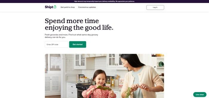This screenshot of the home page for Shipt has a dark header, a white secondary header, and a white main section with dark words reading 'spend more time enjoying the good life' above a photo of a dark-haired woman smiling at a little girl who is playing with a vegetable leaf as they put away groceries.