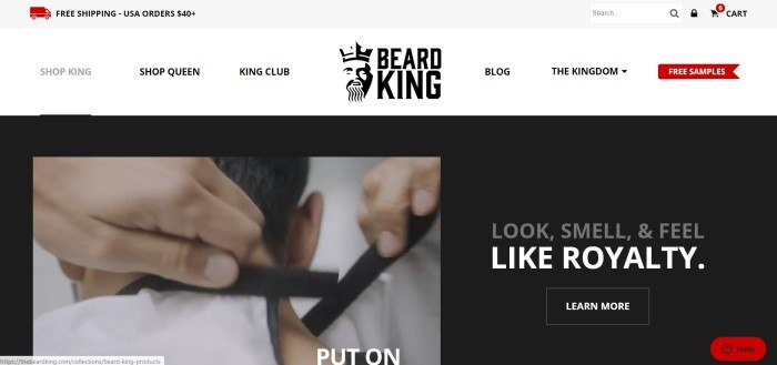 This screenshot of the home page for The Beard King has a gray header, a white navigation bar, and a black main section with a video still shot of a man putting on a beard bib on the left side of the page and text in white and gray lettering on the right side of the page inviting customers to learn more about the products.