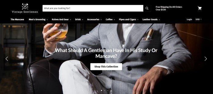 This screenshot of the home page for The Vintage Gentlemen has a dark header and navigation bar with white lettering above a photo of a man from the neck down, dressed in a gray suit with a cigar in the pocket, sitting in what appears to be a leather chair in a luxurious mancave, with glass of whiskey in his hand.