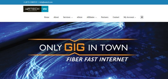 This screenshot of the home page for Watech has a blue header, a white navigation bar, and a large image of white lines, numbers, and letters representing fiber optics, along with white and orange text announcing fiber fast internet.