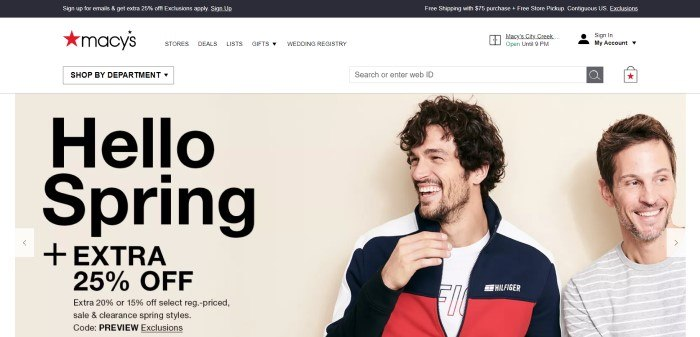 This screenshot of the home page for Macys has a black header, a white navigation bar, and a photo of two smiling men in fashion clothing--one in a white, black, and red jacket and the other in a gray and white striped shirt--next to black text announcing a spring sale.