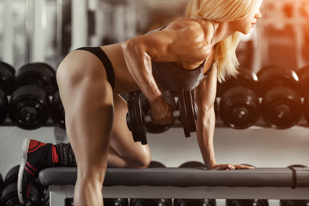 woman bodybuilder on exercise bench with dumbell