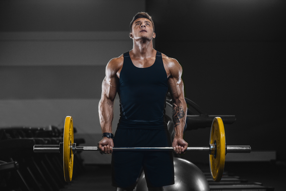young man doing curls with bar bell doing bodybuilding