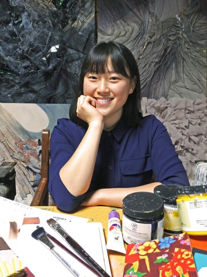 This photo shows a beautiful smiling Asian woman in a blue shirt sitting behind a table full of art supplies and in front of several finished textile art collages in grays and pinks, representing the best fine art affiliate programs.