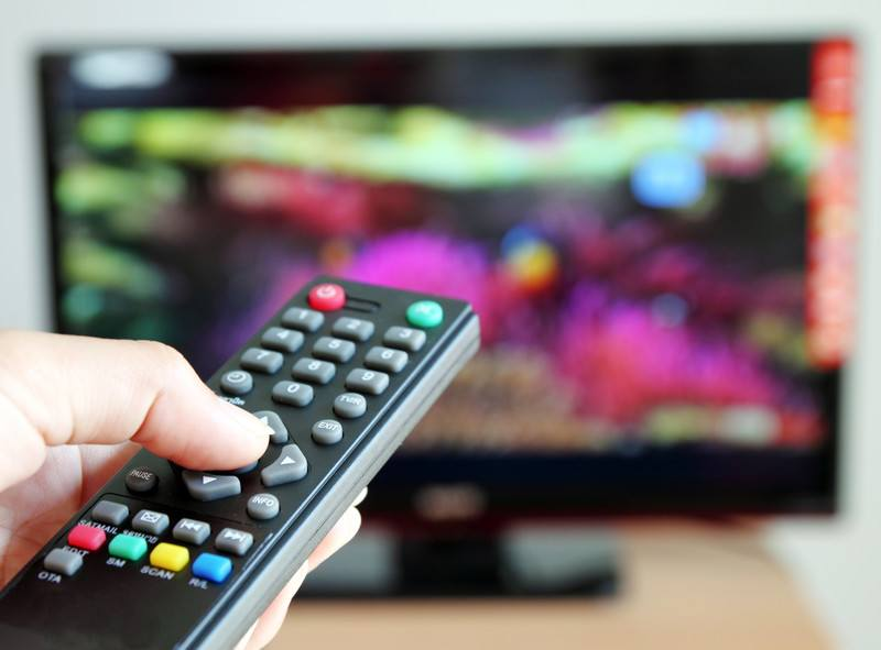 This photo shows a man's hand holding a television remote control, aimed at a blurred but colorful television screen, representing the best internet TV affiliate programs.