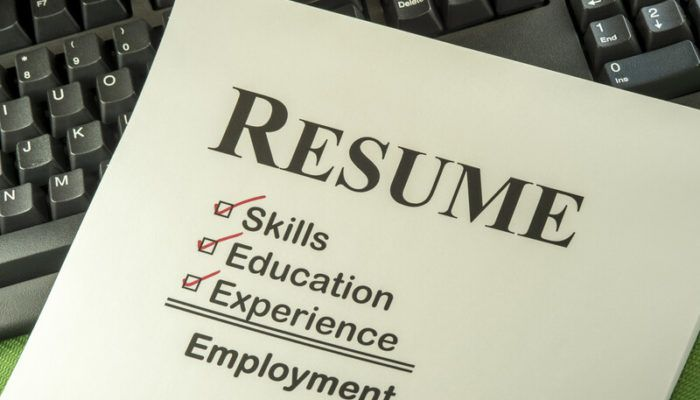 This photo shows a pale yellow resume template lying across a computer keyboard, representing the best resume affiliate programs.
